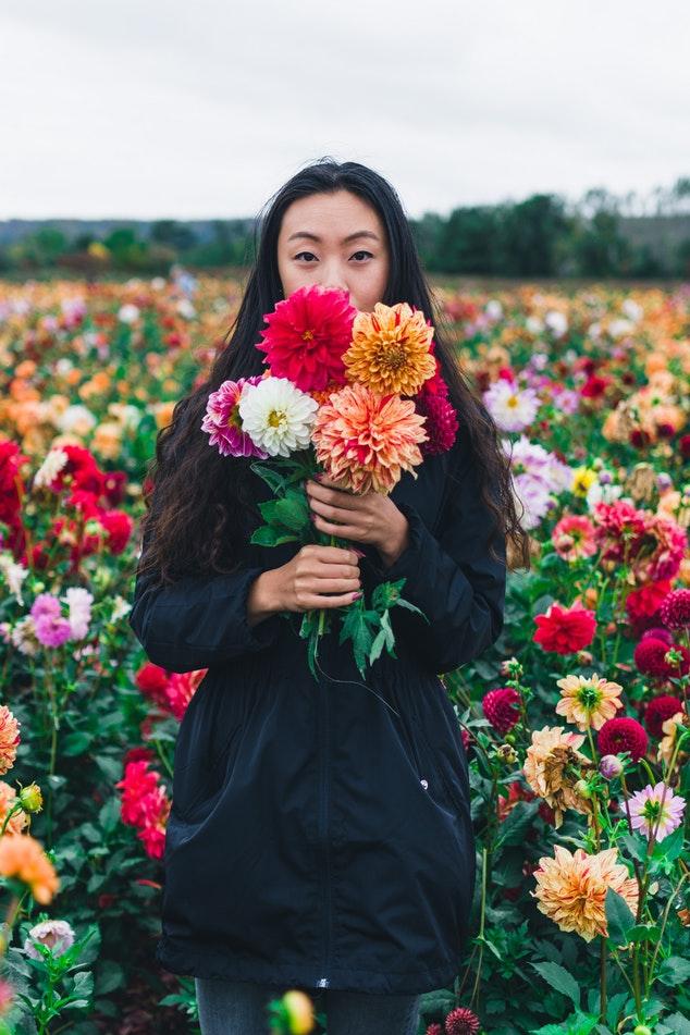 woman holding flowers in a field