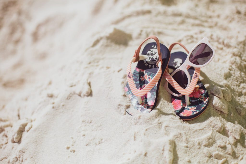Child's flip flops and sunglasses on sand.