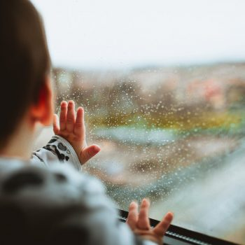 baby looking out a rainy window