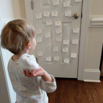 child throwing ball of socks at door