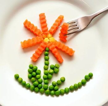 Carrots and peas on plate in the shape of a flower