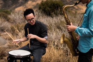 Teen playing drums and Saxophone