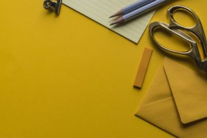 Yellow paper and envelope. Scissors and Pencils.