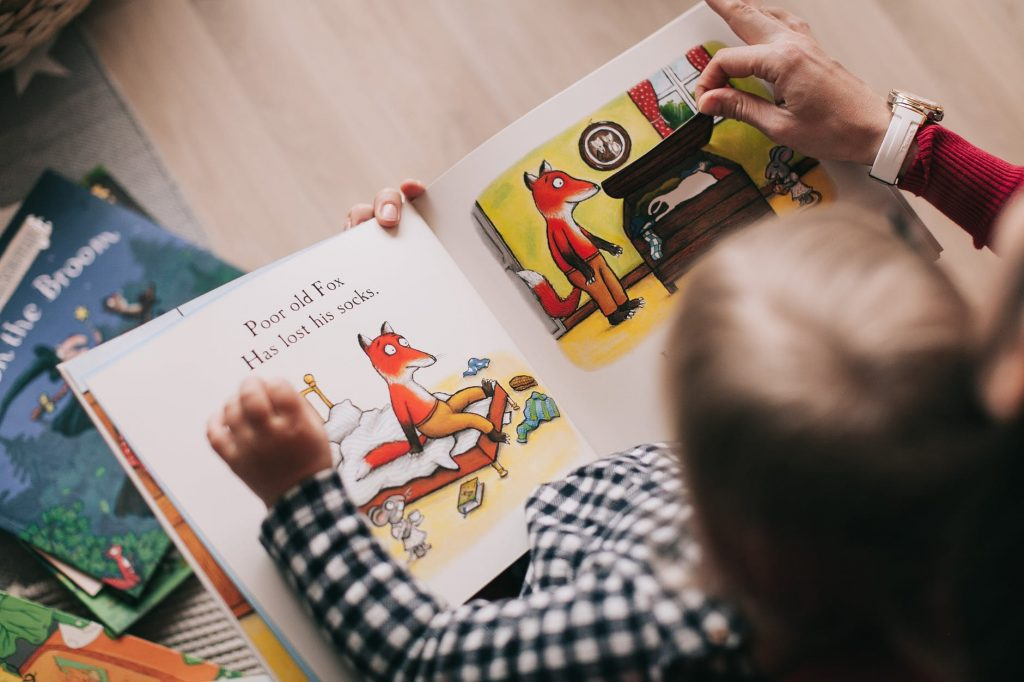 Baby and adult reading a picture book