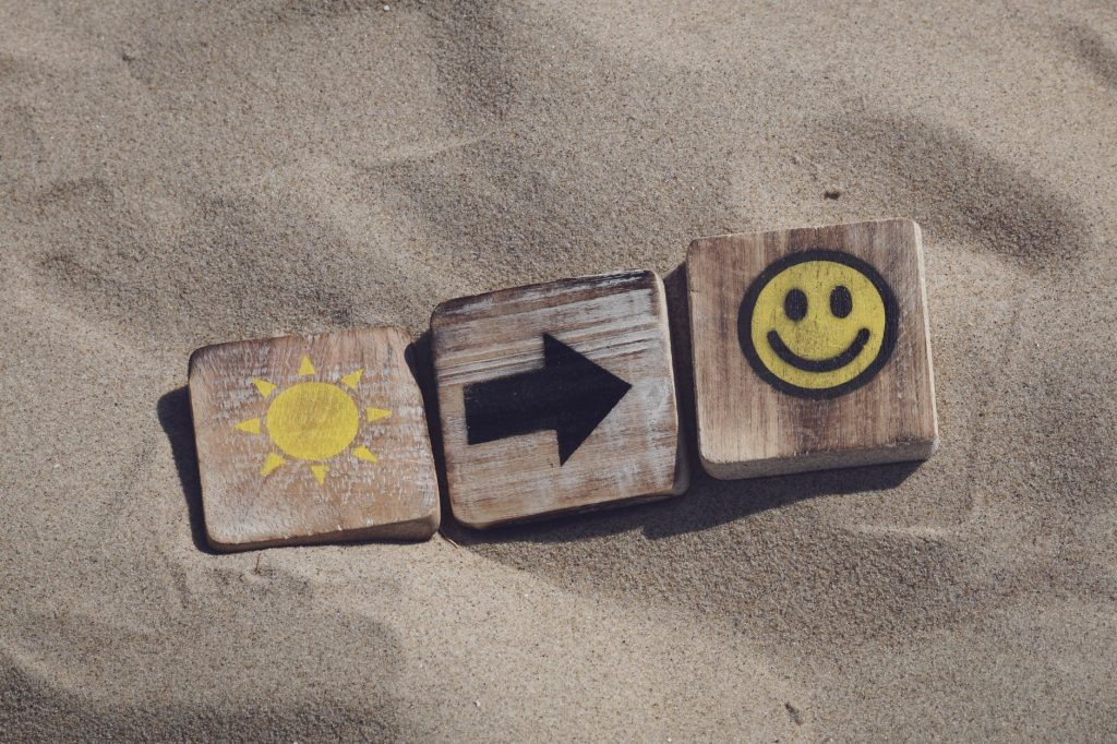Three blocks on sand with a sun, arrow, and smiley face on them.