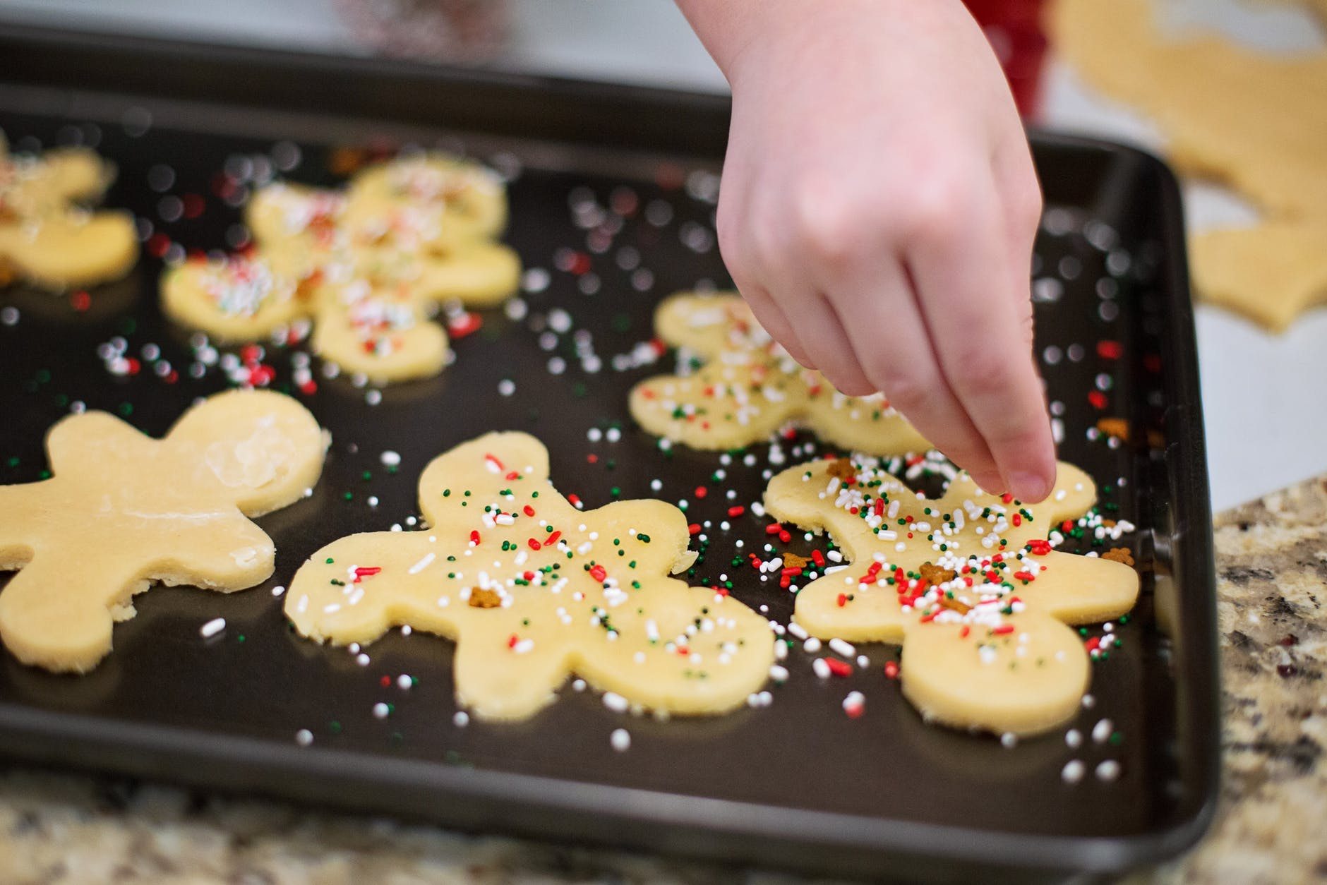 child's hand decorating cookies with sprinkles