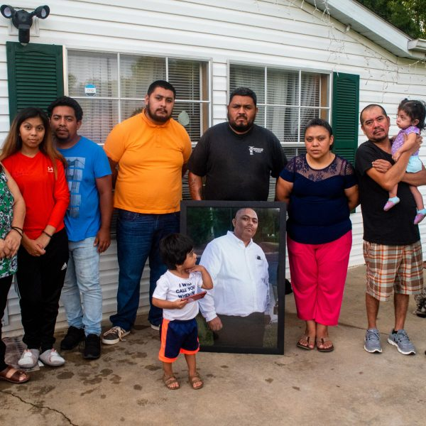 Members of the Chagoyan family stand outside their home in Midland, North Carolina, holding a portrait of Juan Chagoyan, who died July 20. LAURA BRACHE, WFAE